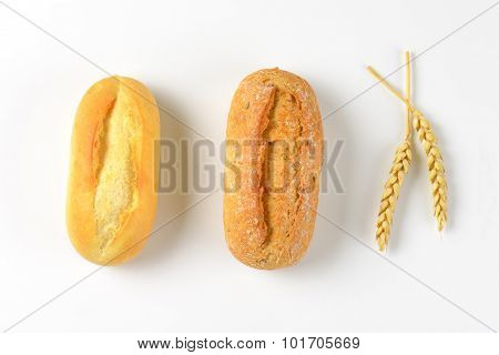 two freshly baked bread rolls on white background