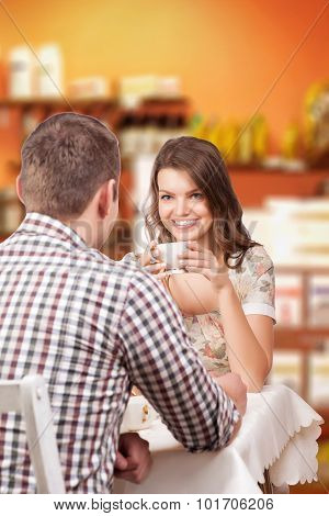 Seducing beautiful woman looking at her lover with coffee cup. Having romantic talk photo