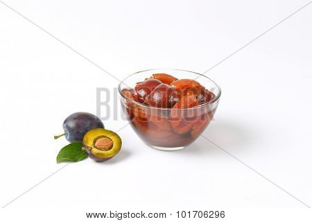 fresh plums and bowl of preserved plums on white background