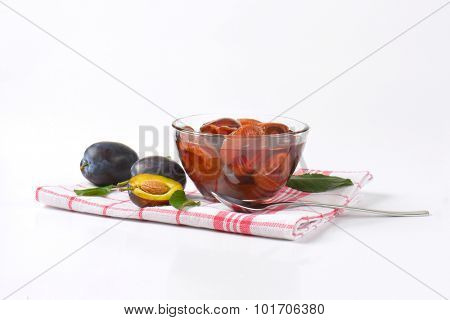 fresh plums and bowl of preserved plums on checkered dishtowel