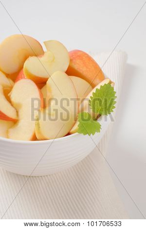 bowl of apple slices on white place mat