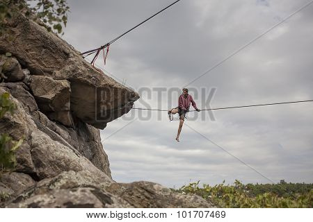A Man Walks Down Slackline.