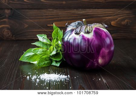 Eggplant (aubergine) and basil on dark wooden table. Fresh raw farm vegetables - harvest from the ga
