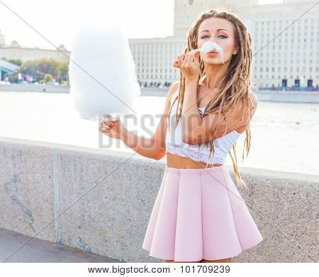 Beautiful fashionable Girl eating cotton candy have fun in warm summer evening on the banks of the r