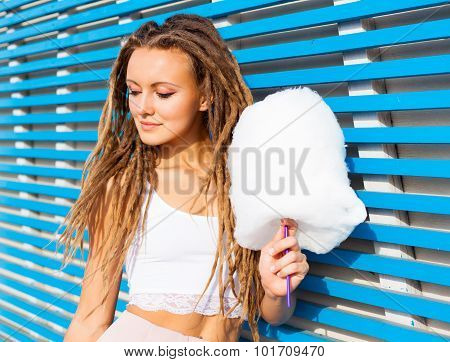 Beautiful young woman with dreads posing near blue plank wall with cotton candy summer warm evening