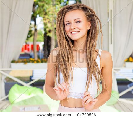 Beautiful young girl with dreadlocks in a summer cafe a sunny summer day. Outdoor