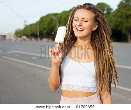 Young sexy blonde girl with dreads eating white ice cream in summer hot evening,  joyful and cheerfu