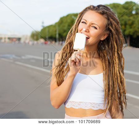 Young sexy blonde girl with dreads eating white ice cream in summer hot evening,  have fun and good
