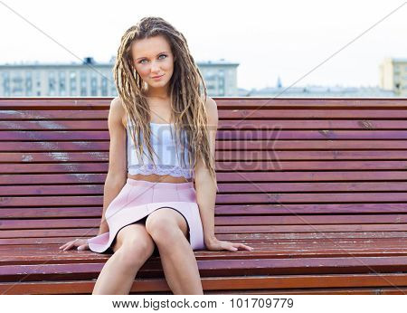 Sad lonely girl sitting on a bench a warm summer day in the city