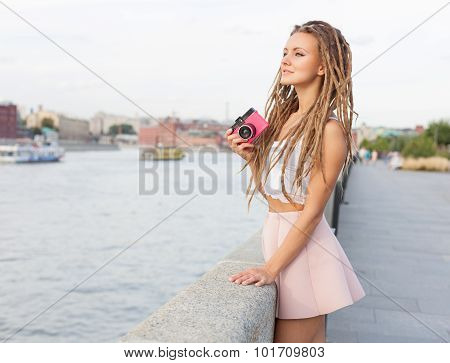 Portrait of Trendy Girl with Dreads and Vintage Camera Standing by the River. Modern Youth Lifestyle