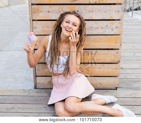 Beautiful girl with dreadlocks in pink skirt sitting on the veranda and eating colorful ice-cream co