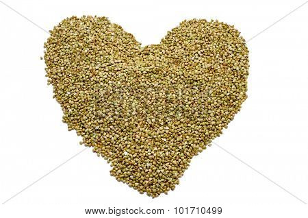 a pile of buckwheat seeds forming a heart on a white background