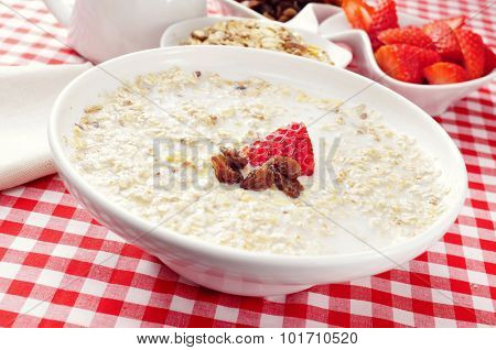 closeup of a bowl with porridge with sultana raisins and strawberry, on a set table with a checkered tablecloth for breakfast