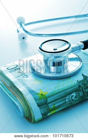 a stethoscope on a wad of euro bills, depicting the concept of the health care industry or the health care costs