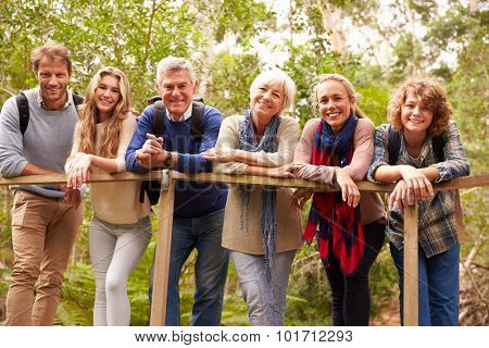 Multi-generation family on a bridge in forest, portrait