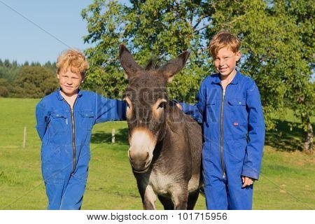 Farm boys posing with their donkey
