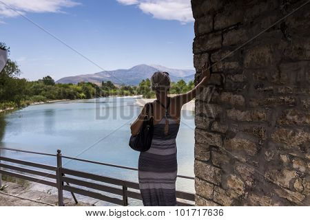 Woman Standing On The Bridge Looking At The View Of Arachthos River Of Arta City, Epirus Greece
