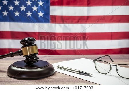 Gavel and glasses on a wooden table, American flag background
