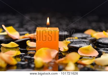Orange rose petals with candle and therapy stones