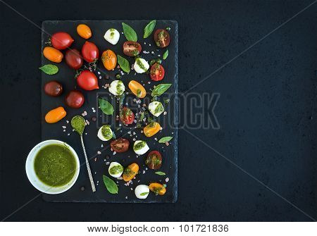 Caprese set. Cherry tomatoes of various color, mozarella, basil leaves, spices and pesto sauce on bl