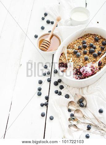 Healthy breakfast. Oat granola berry crumble with fresh blueberries, yogurt and honey in ceramic bak