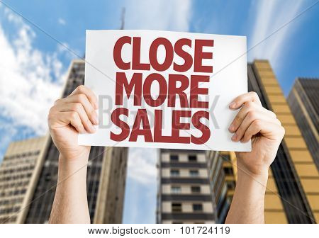 Close More Sales placard with cityscape background