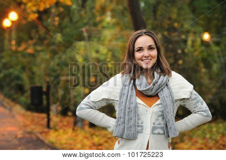 Smiling woman wearing knitted jacket in autumn evening park.