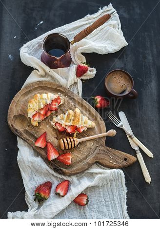 Breakfast set. Freshly baked croissants with strawberries, mascarpone, honey and coffee on rustic wo