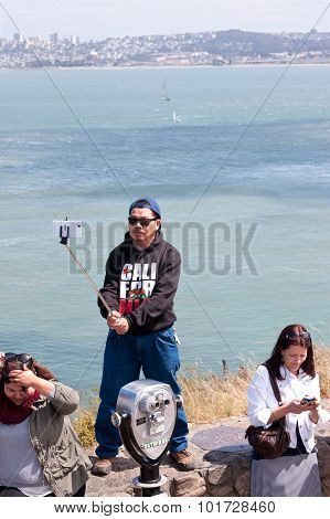 Man Holds Selfie Stick Taking Photo At San Francisco Bay