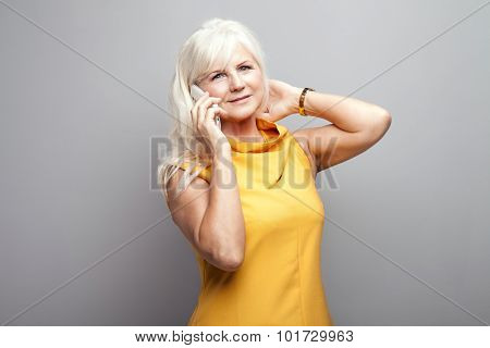 Senior Woman Talking By Mobile Phone In Studio.