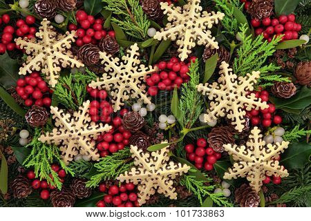 Christmas abstract background with gold snowflake bauble decorations, holly, ivy, mistletoe, blue spruce fir and cedar cypress greenery.