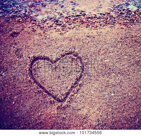 a heart written in the sand for an i love you concept toned with a retro vintage instagram filter app or action effect