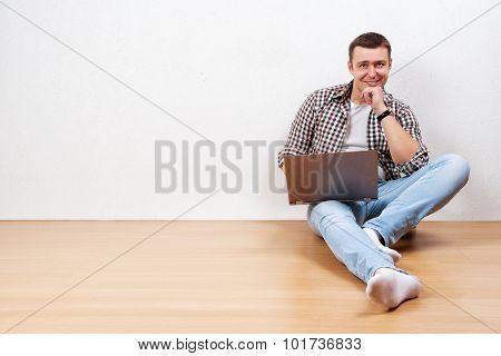 Young Man Looking Thoughtful And Using Laptop