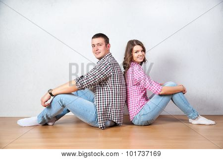 Young Couple Relaxing On The Floor At Home Sitting Barefoot Back To Back Each Looking Up