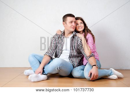 Beautiful Barefoot Young Couple In Casual Jeans Sitting Leaning Against A White Wall On The Wooden F