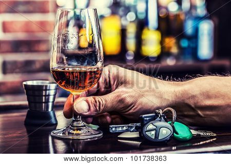 Cup cognac or brandy hand man the keys to the car and irresponsible driver.