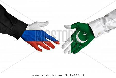 Russia and Pakistan leaders shaking hands on a deal agreement