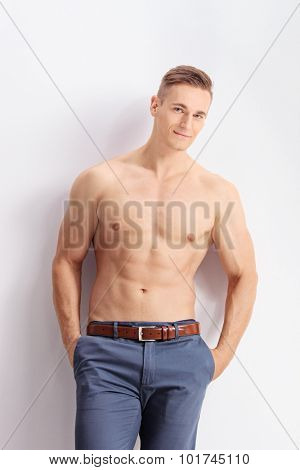 Vertical shot of a handsome shirtless man leaning against a wall and looking at the camera
