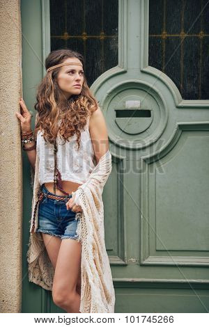 Young Trendy Hipster Woman Standing Outdoors Against Wooden Door