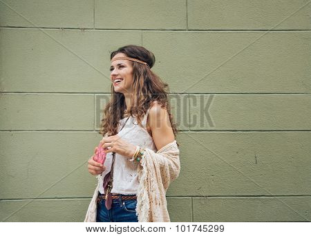 Happy Trendy Hipster Woman Standing Against Wall Outdoors