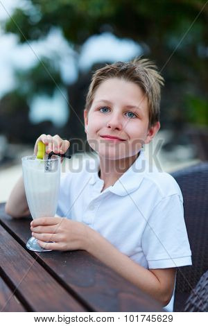 Teenage boy drinking milkshake in outdoor cafe