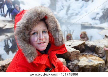 Teenage boy at Snow monkey Japanese Macaque park looking at monkeys bathe at onsen hot springs in Nagano, Japan