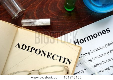 Hormone adiponectin written on book.