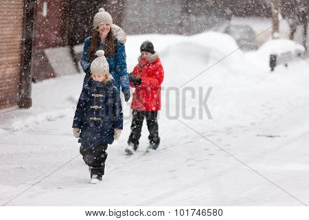 Family of mother and kids outdoors on cold winter day walking under heavy snowfall