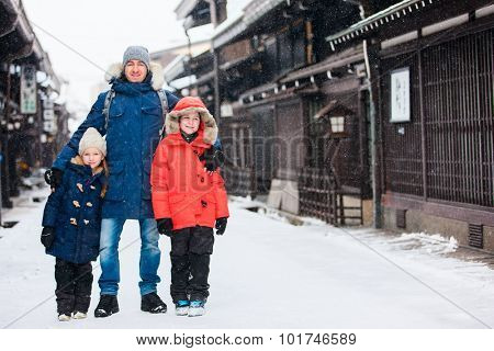 Family of father and kids at old district of historical Takayama town in Japan on winter day
