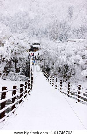 People crossing the bridge over Shogawa river at historic Japanese village Shirakawa-go at winter, one of Japan's UNESCO world heritage sites
