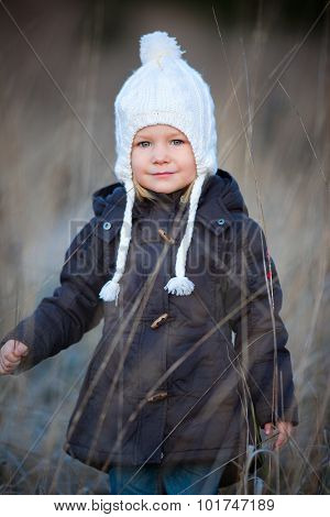 Portrait of adorable little girl wearing parka outdoors on cold winter day