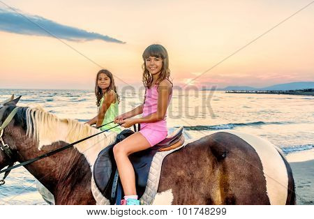 Twin Sisters Riding Horses In The  Sunset By The Sea On The Island Of Ada Bojana, Montenegro