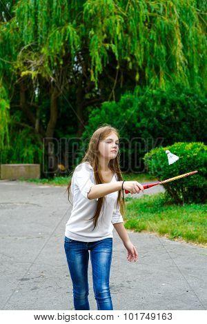 Portrait of happy girl holding badminton racket and shuttlecock