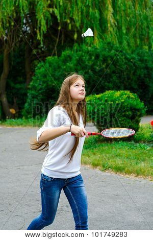 Portrait of happy girl holding badminton racket and shuttlecock